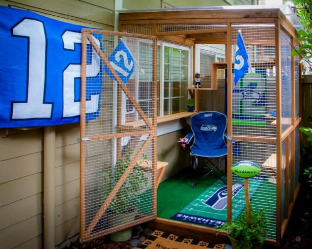 a cat enclosure with a Seattle Seahawks American football theme and a window door insert