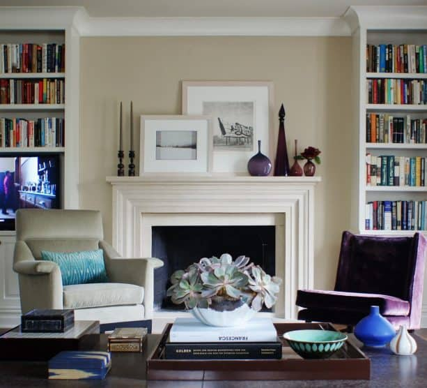 a pair of built-in bookshelves with crown molding at the top matched with a traditional fireplace in antique white