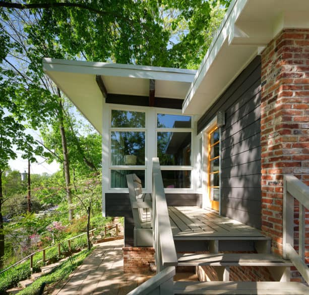 a contemporary exterior with red brick and charcoal grey siding combination