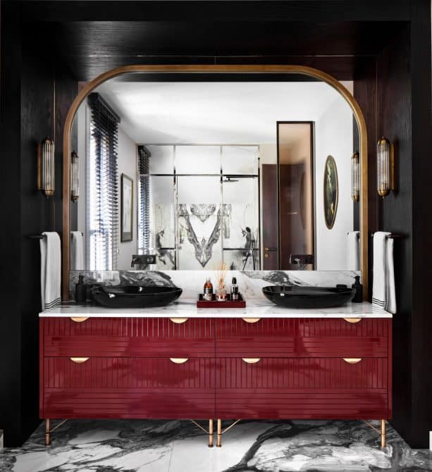 a luxurious red and gold vanity placed in front of a black wall surround