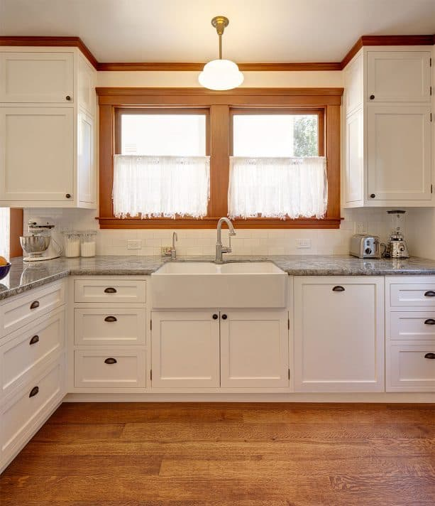 the beautiful combination of stained-wood crown molding and white cabinets in a craftsman kitchen interior