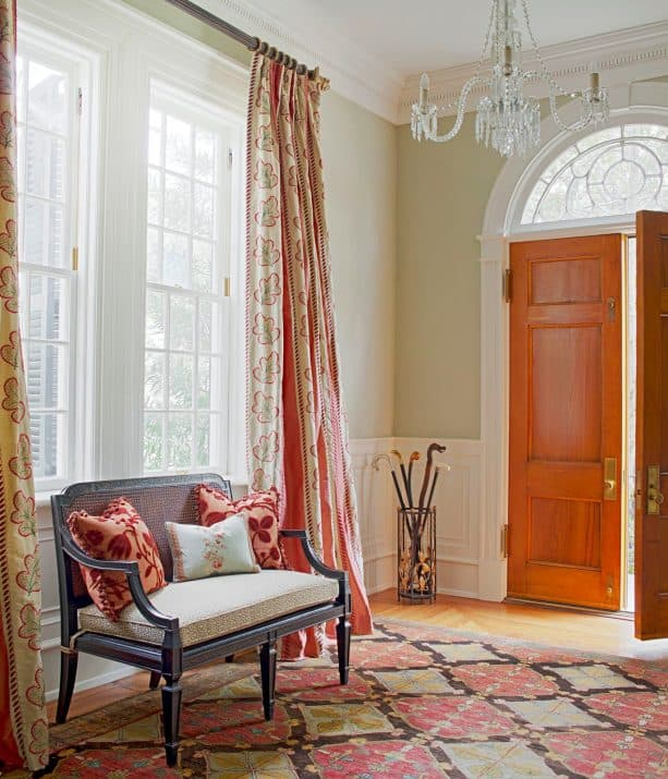a traditional entry with warm color domination, wood door, and white trim