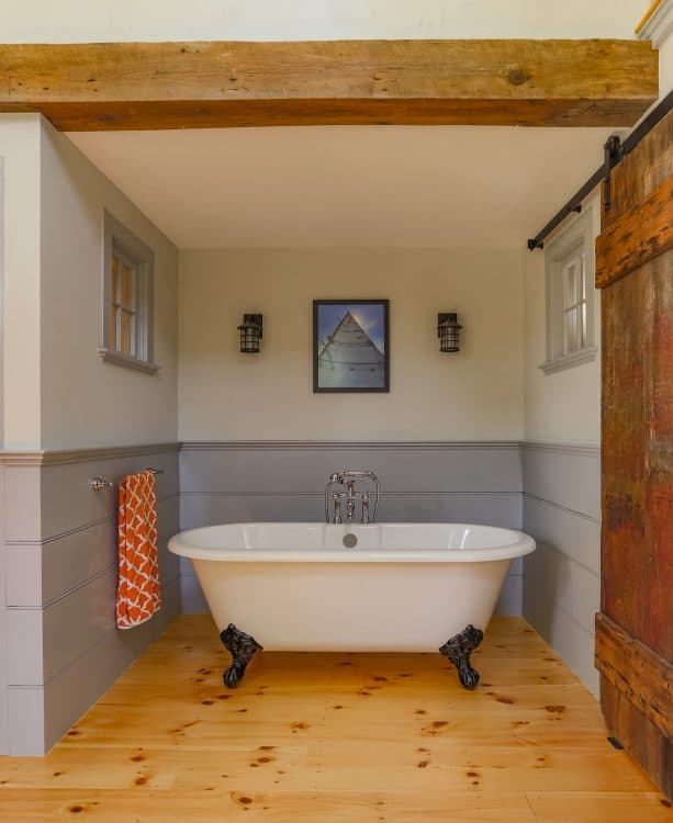 the barn door slides in front of the wall on the tub side