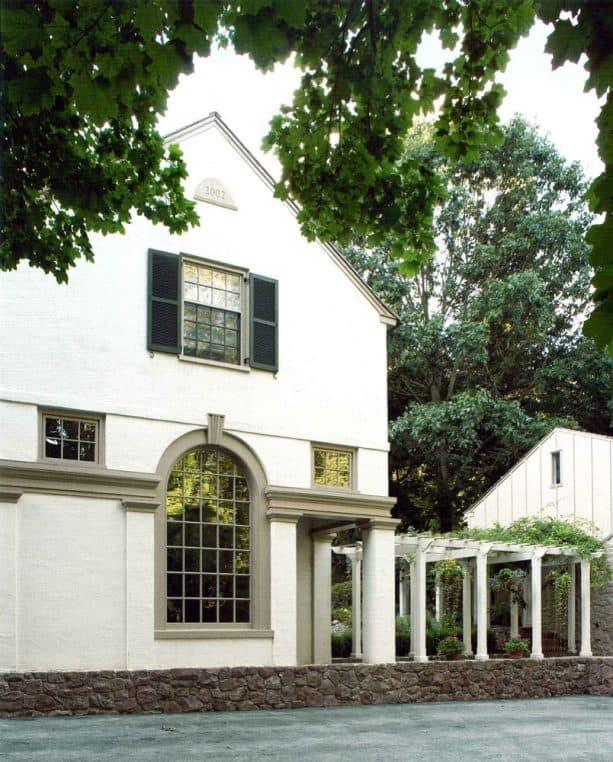 a cream-white house with greige exterior trim around the windows