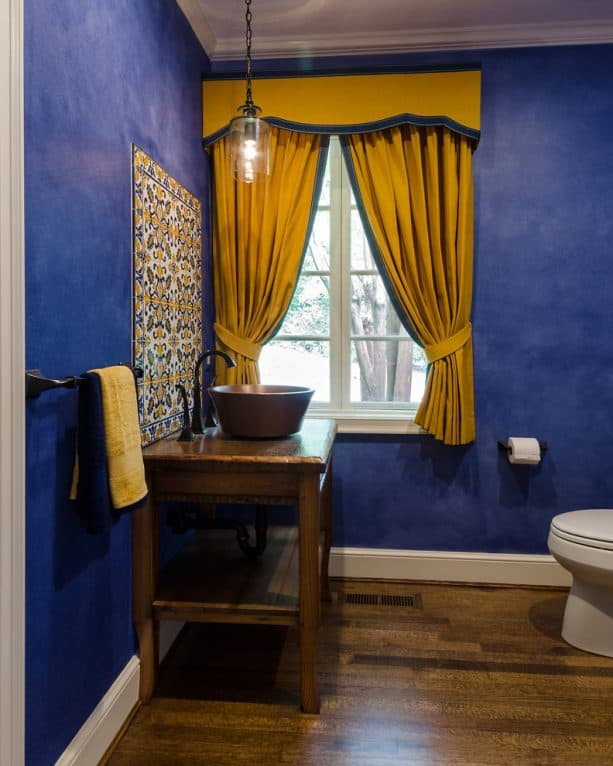 vibrant blue walls and yellow curtains combo in a Mediterranean bathroom