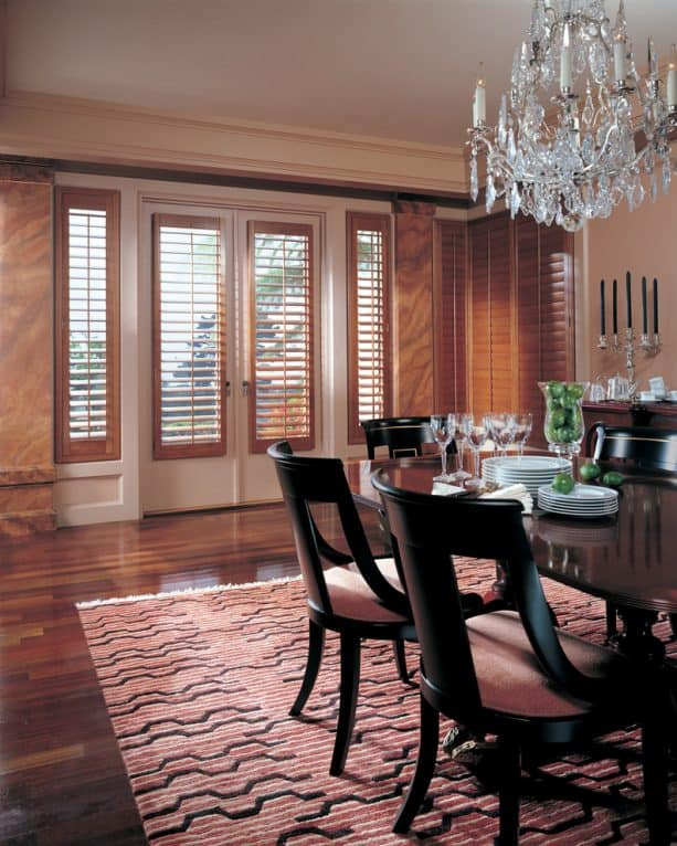 French door glasses covered by brown-stained plantation shutters
