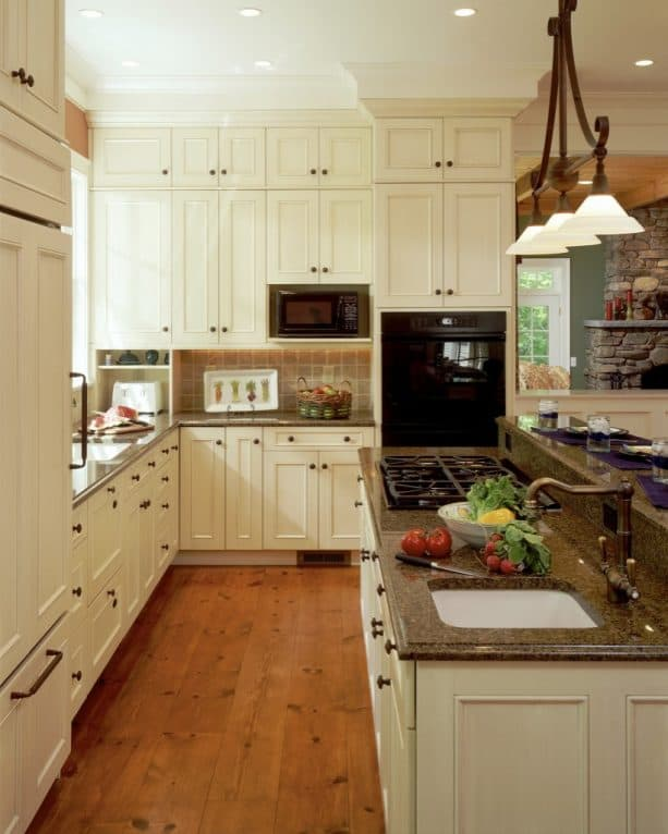 an elegant traditional kitchen design with creamy white cabinets, copper knobs, and brown granite for the countertops