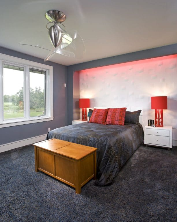 contemporary bedroom with charcoal grey and white walls, red accents, and glass windows