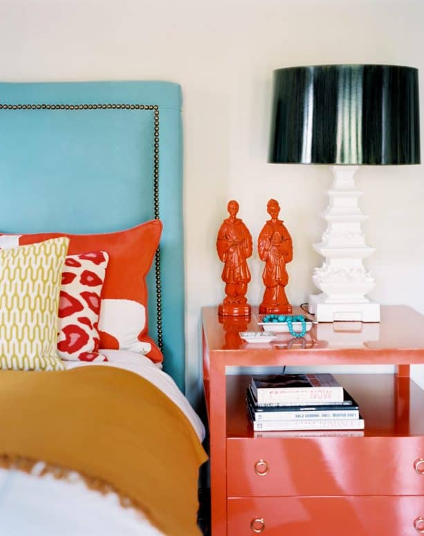 a turquoise headboard paired with tangerine bedside table and decorations