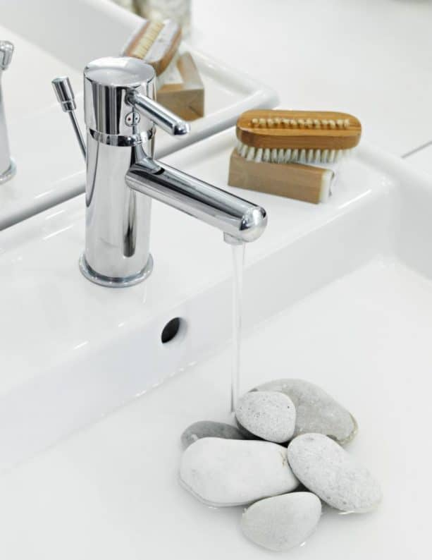 a white modern bathroom vanity sink with white river stones covering the drain