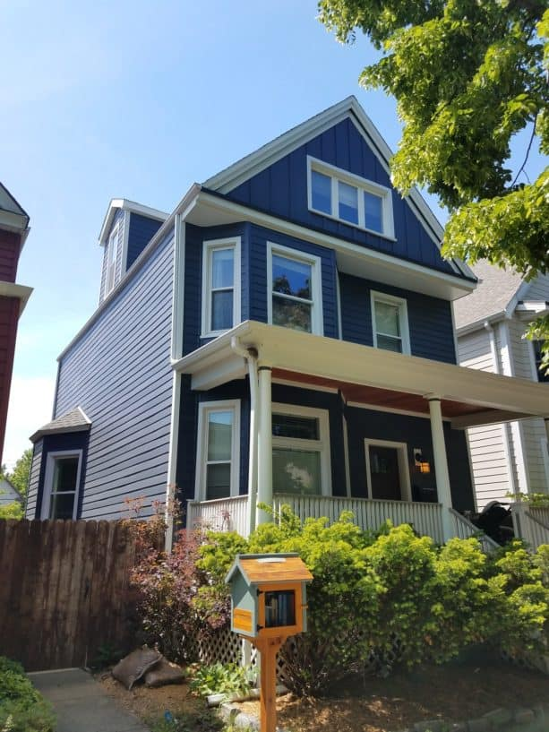 a traditional house with deep ocean blue paint siding and white trim