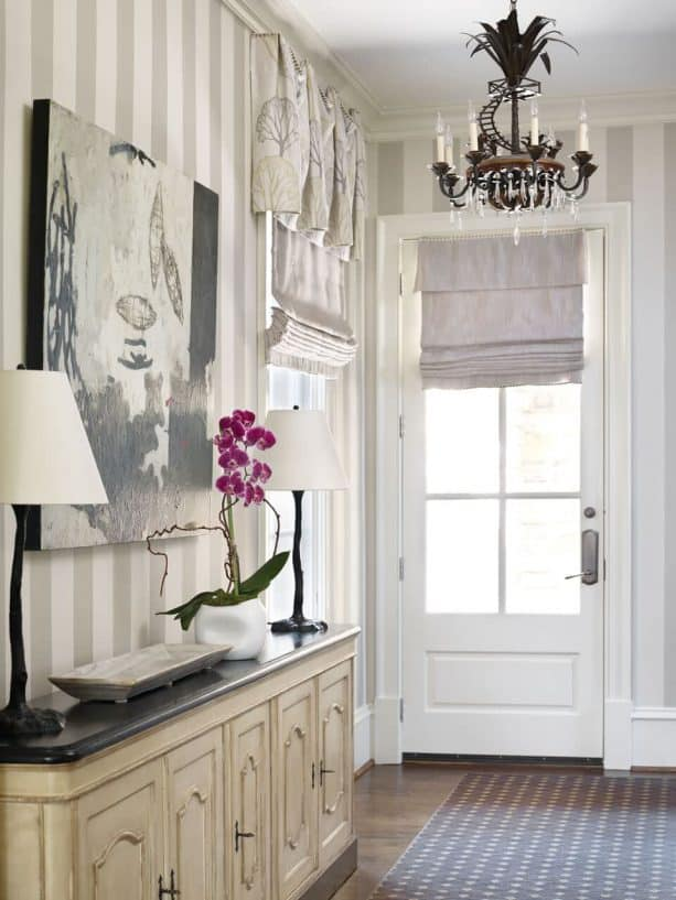 an off-white blackout roman shade covering a traditional half glass door entry