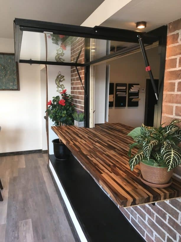 a flip out black pass through window paired nicely with unique continuous wooden counter
