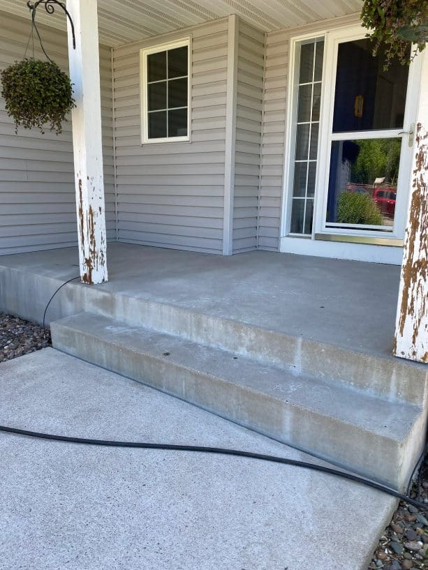 the concrete steps and porch after being prepared for the makeover