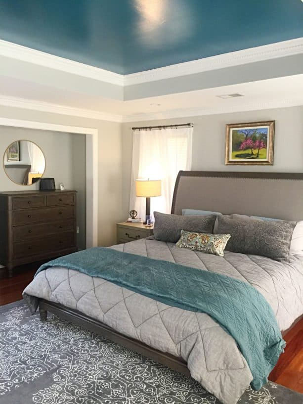a transitional bedroom with a cloud gray wall and teal ceiling
