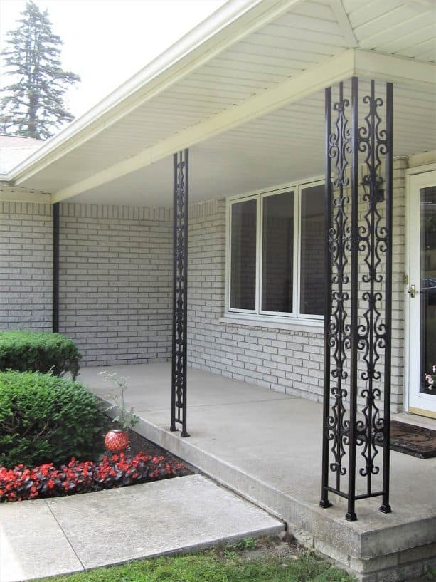black wrought iron columns are perfect for a traditional concrete porch