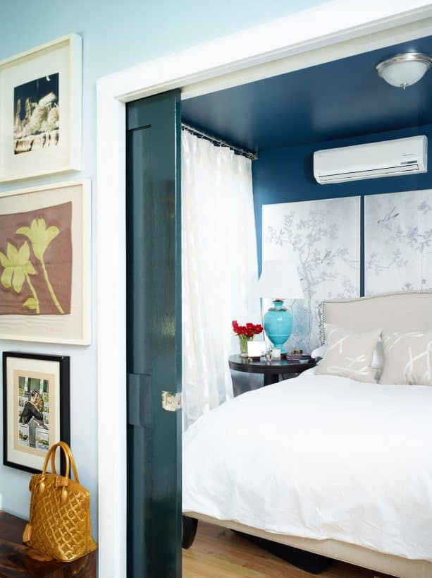 a bedroom with peacock blue walls and sheer white curtains