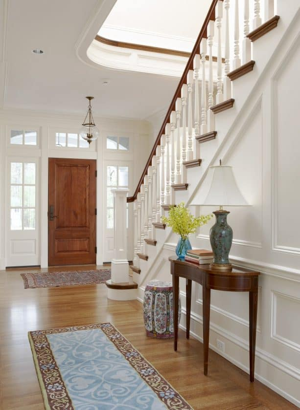 a wood door and white trim that look matching with the staircase design