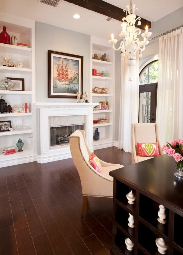 crisp white fireplace with tiles surround and built-in shelves around