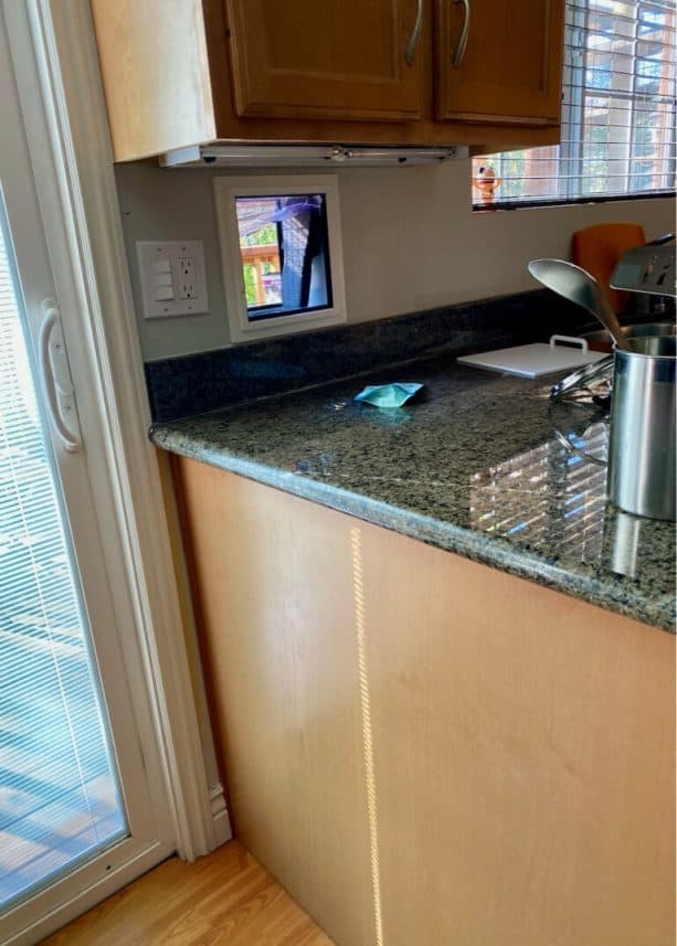 The cat door insert is located on the wall near the kitchen counter