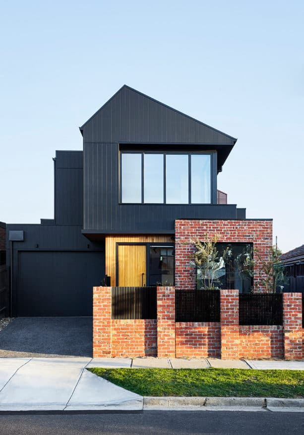 a contemporary house with black siding and red brick