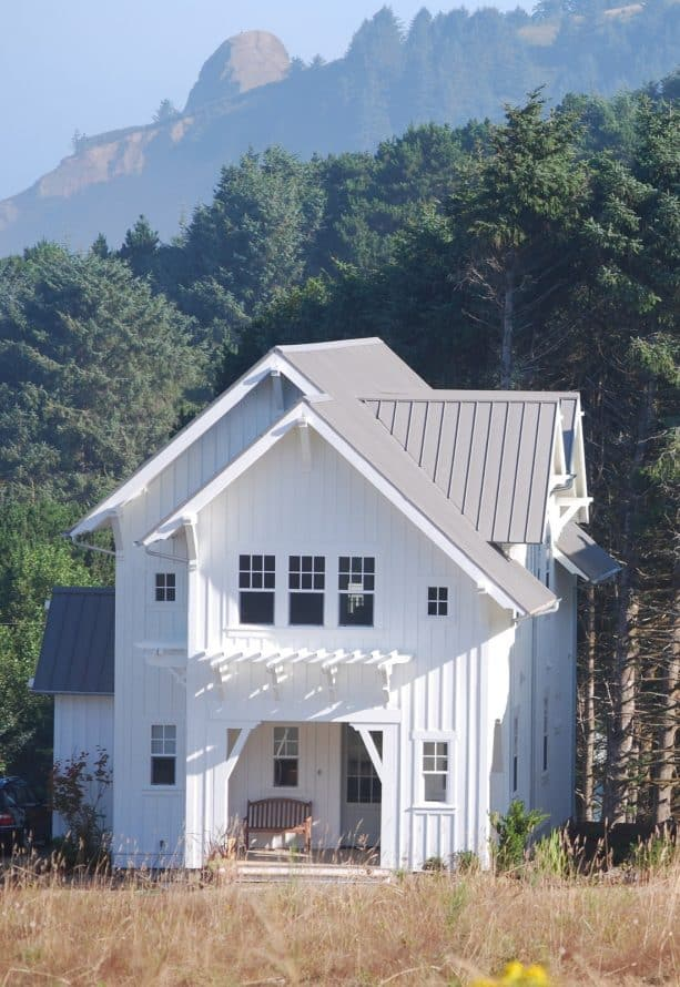 a white-painted farmhouse-style mountain home with grey roof