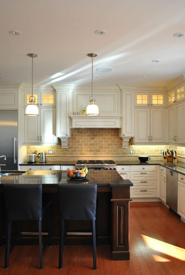 cream kitchen cabinets paired with subway stone tile backsplash