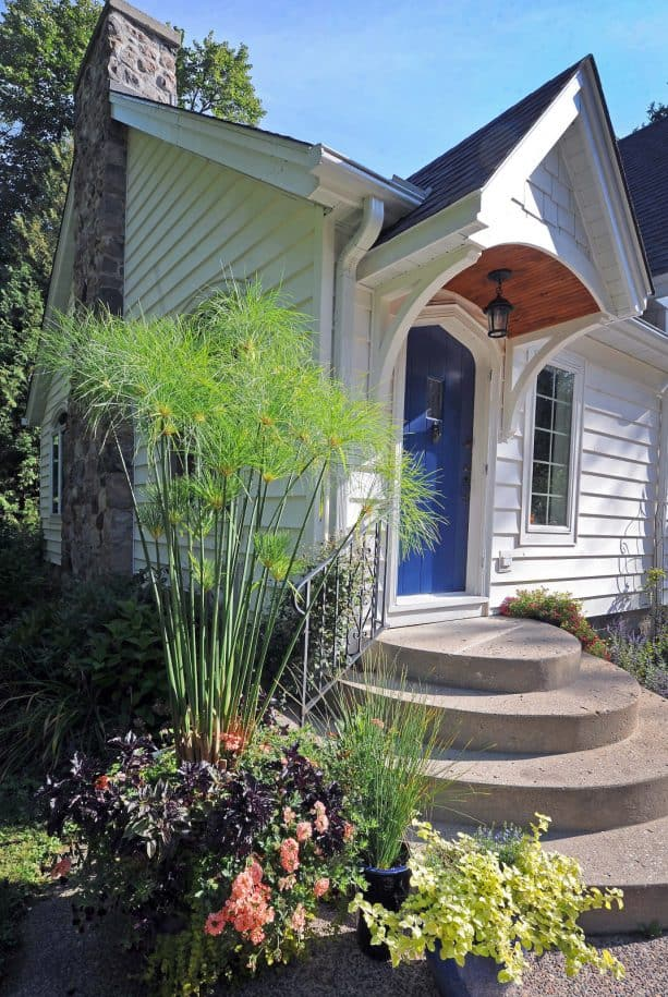 a small transitional wood exterior home with a benjamin moore down pour blue front door