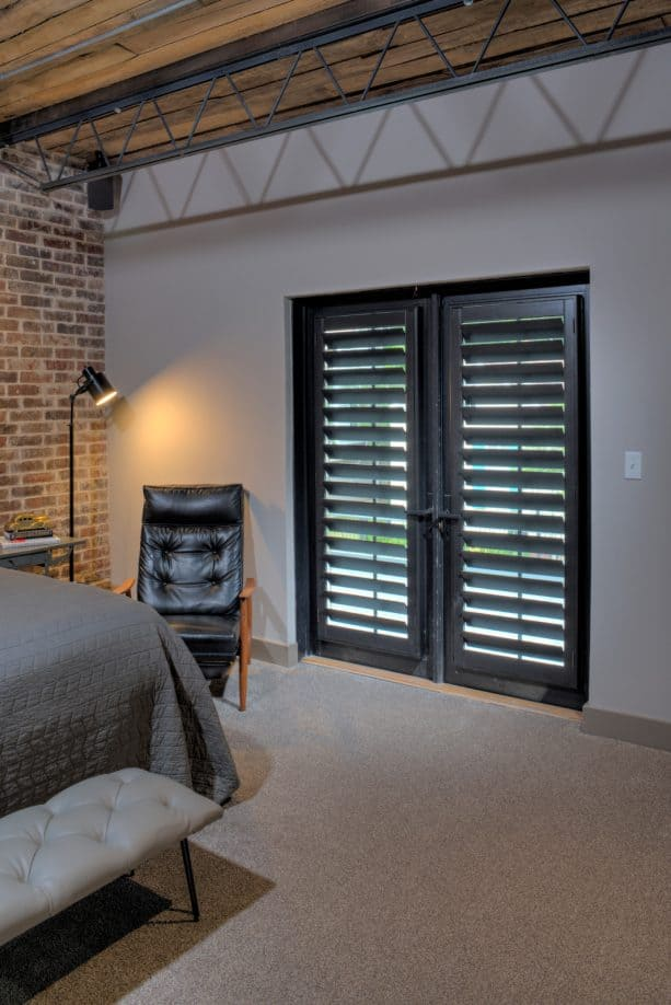 black French doors with stained black plantation shutters as the cover