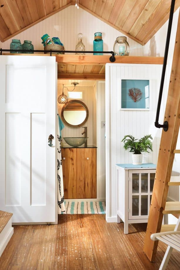 a small bathroom with barn door in a tiny beach house