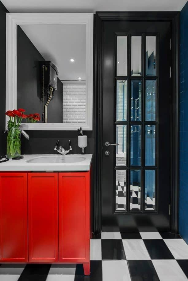 unique contemporary bathroom interior with black walls, black French door, and bright red vanity