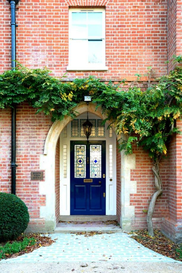 a stunning navy blue door paired with red brick wall