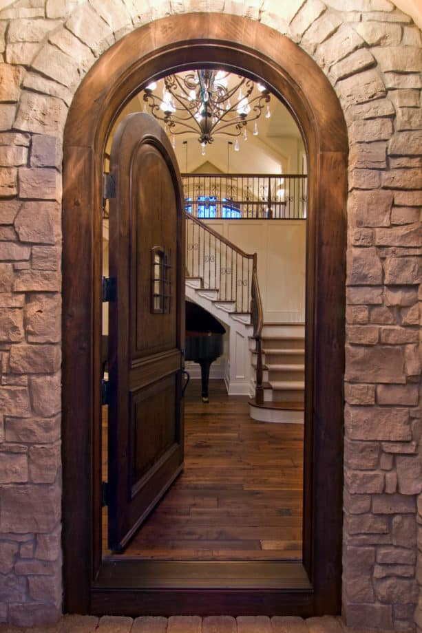 a traditional arched wooden front door with trim stained in the same color