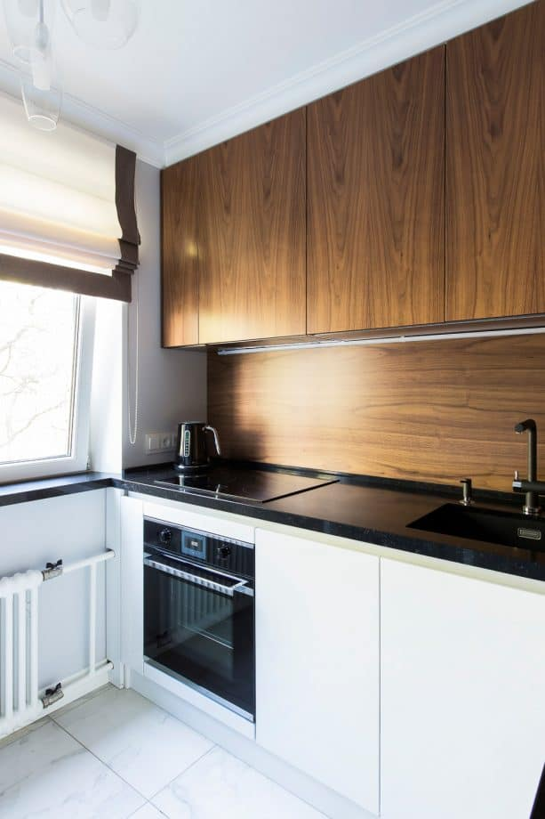 a contrast look from medium tone wood kitchen backsplash and glossy black countertops