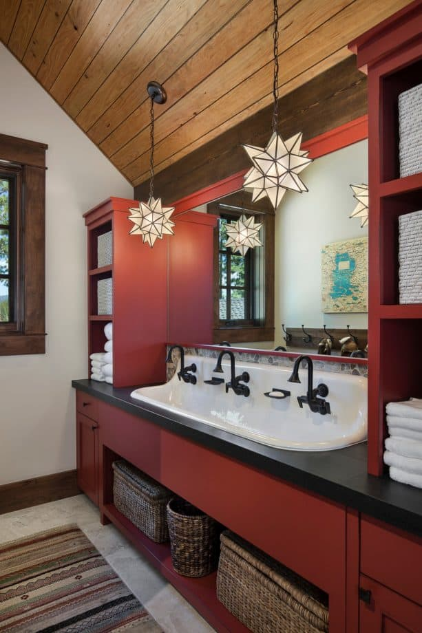 a matte red custom vanity with black countertop and hardware in a rustic bathroom