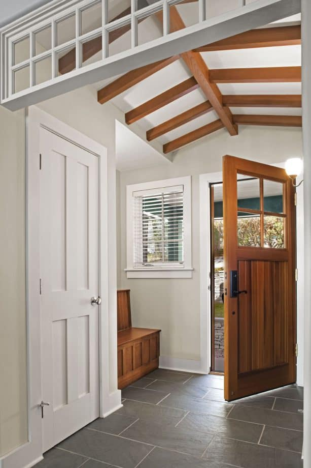 a medium tone wood door with white trim in a transitional entry