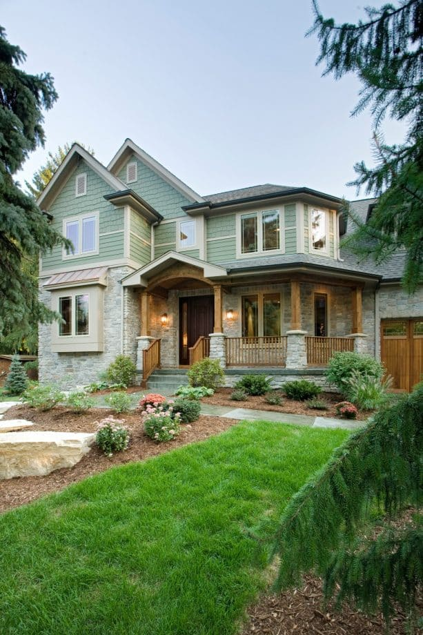 home exterior with the combination of sage green color and grey stone material