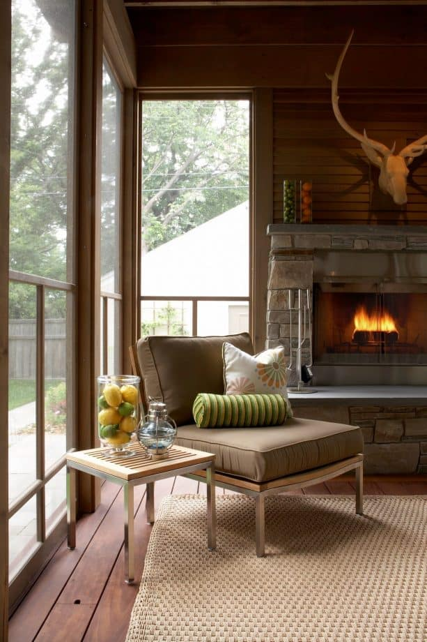 a screened porch with a reading spot near the fireplace