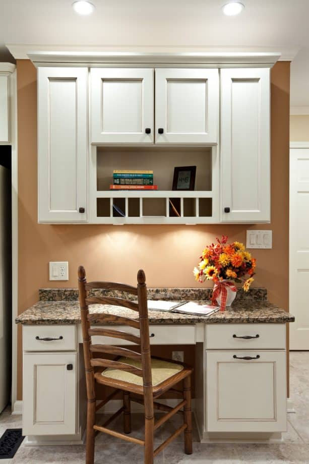 a kitchen desk cabinet with glaze, white color, and brown granite countertops
