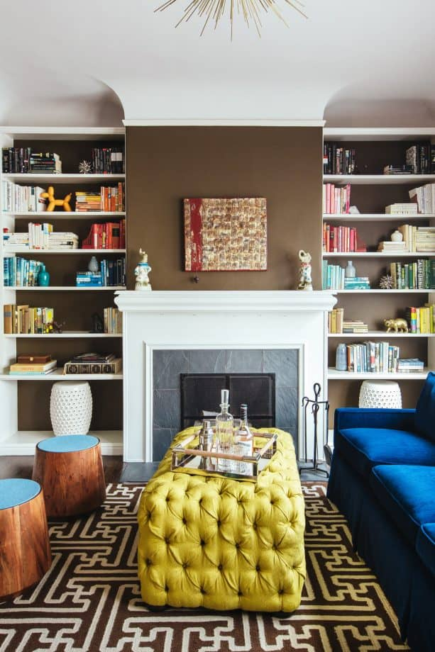 a white fireplace matched with simple yet unique bookshelves with brown wall as the back panels