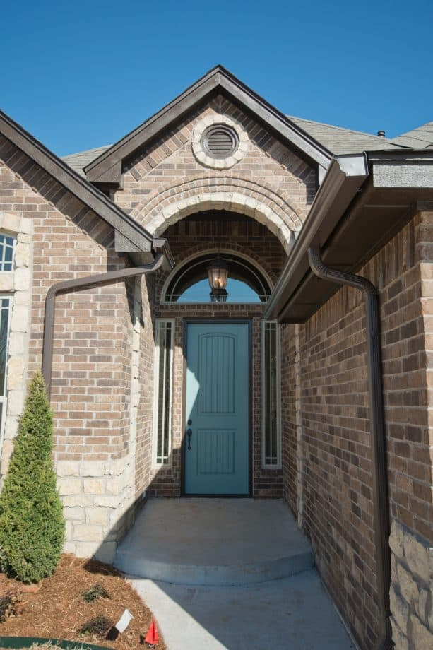 a large brick traditional house completed with a sherwin williams dark moody blue front door
