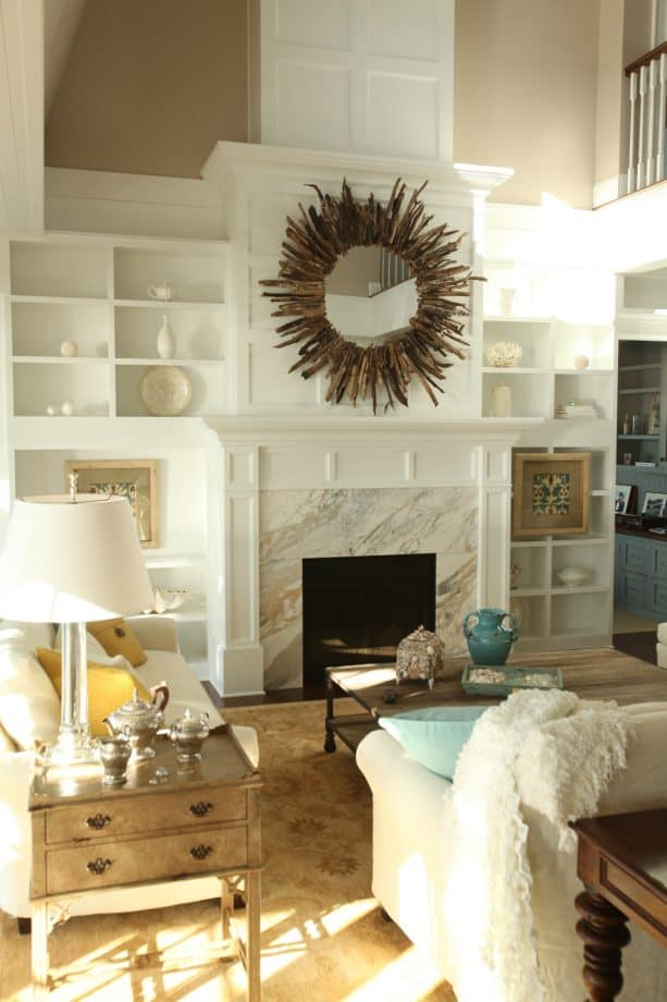 glacier white built-in shelves around a calcutta gold marble fireplace
