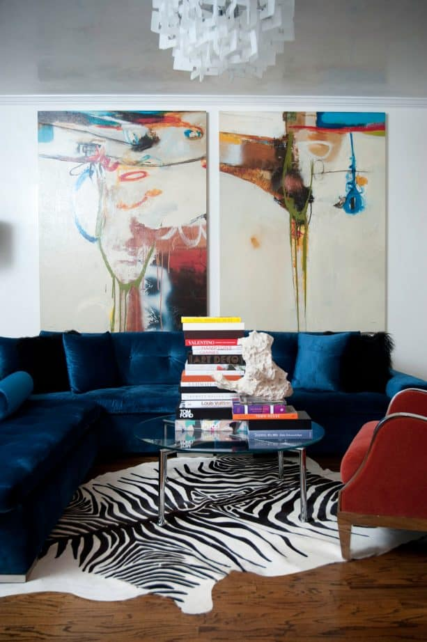 navy blue velvet sectional sofa and red chair in a contemporary living room