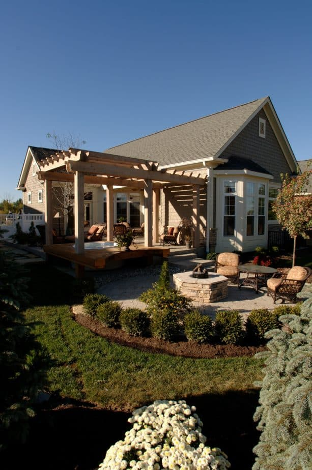 attached pergola on a raised stone patio with a hot tub