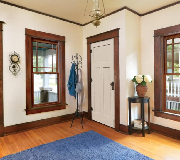 a traditional interior with off-white door and stained oak wood trim