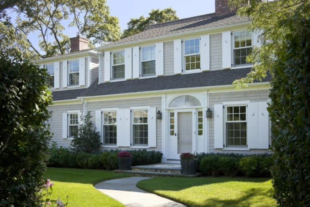 a classic traditional exterior with tan shingle siding and white shutters