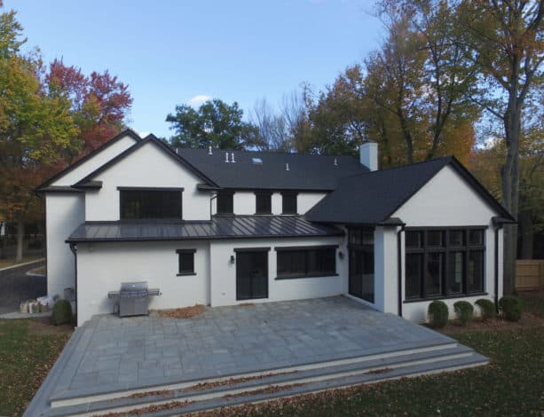 a transitional white house with black roof and trim