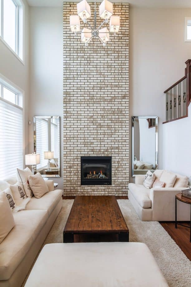transitional living room with chiffon white wall paint and greige wall-size brick fireplace
