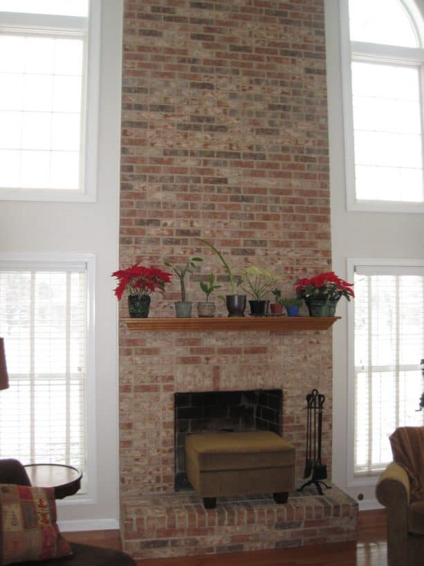 before makeover tall floor to ceiling brick fireplace with raised hearth no insert