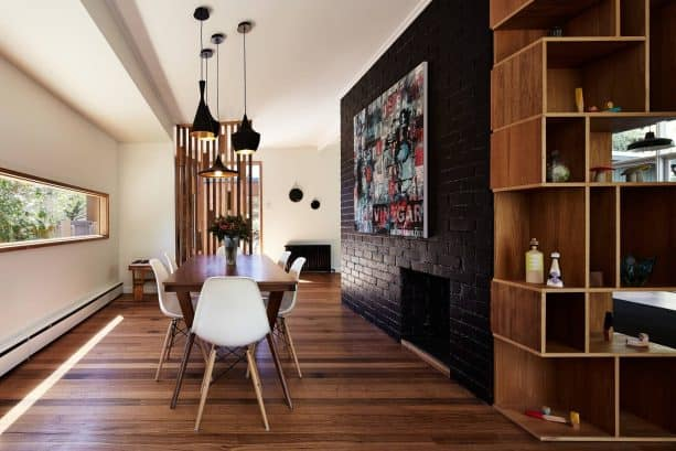contemporary dining room with black brick fireplace and accent wall